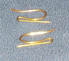 two small bronze clips folded in a narrow S-curve with one pointy end.