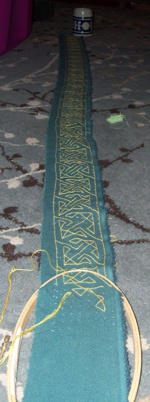 six feet of narrow yellow-on-green backstitched in a Cetic key design.
